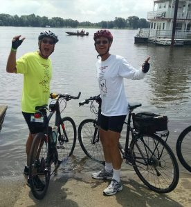 Rod and Dennis Carlson (right) do the official dipping of their front tires in the Mississippi River at Muscatine, Iowa.