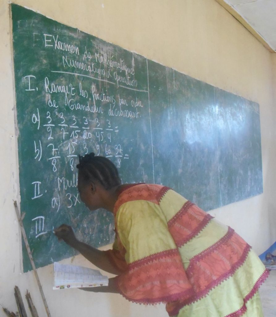 A teacher in Gemena writes an exam in classroom constructed with Covenant Kids Congo funds.